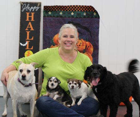Business owner smiling with four dogs